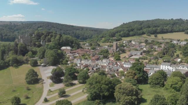 vídeos de stock e filmes b-roll de aerial drone shot of the village of dunster near minehead, england, united kingdom. - por volta do século 11 dc
