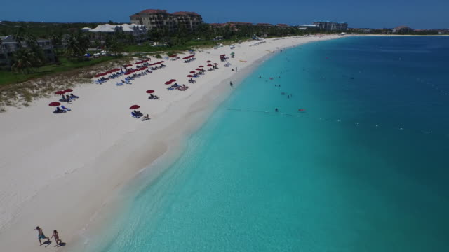 Aerial drone shot of tourists by the beachside / Provodenciales, Turks and Caicos Islands