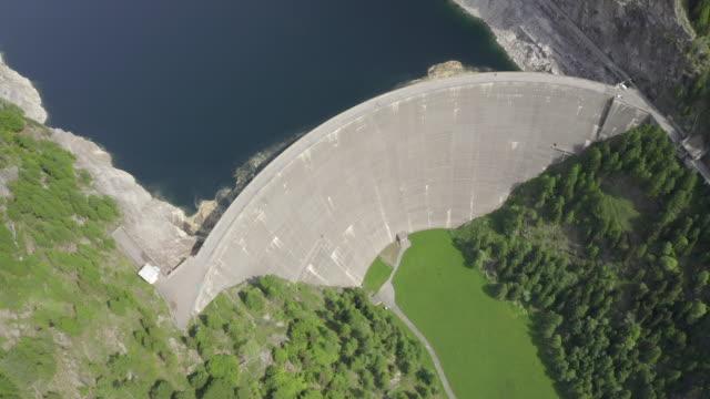 aerial drone shot of two bikers crossing a dam in ticino switzerland - wasserkraft stock-videos und b-roll-filmmaterial