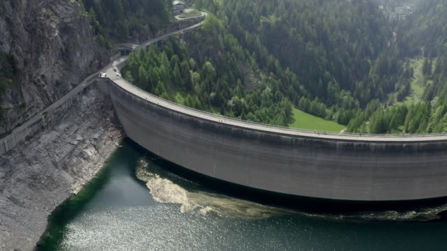 aerial drone shot of two bikers crossing a dam in ticino switzerland - sustainable energy stock videos & royalty-free footage