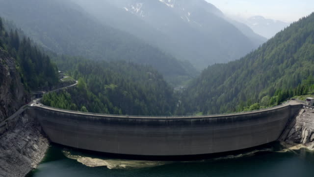 aerial drone shot of two bikers crossing a dam in ticino switzerland - sustainable energy stock-videos und b-roll-filmmaterial