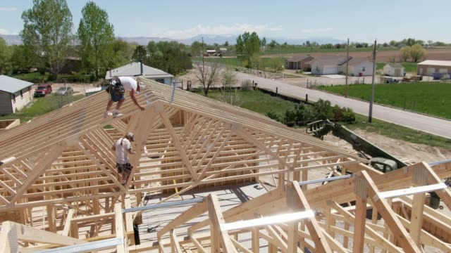 aerial drone shot of two caucasian male construction workers framing a house on a sunny day - legname video stock e b–roll