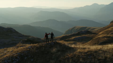 aerial drone shot of two hikers celebrating on top of a mountain vista - stehen stock-videos und b-roll-filmmaterial
