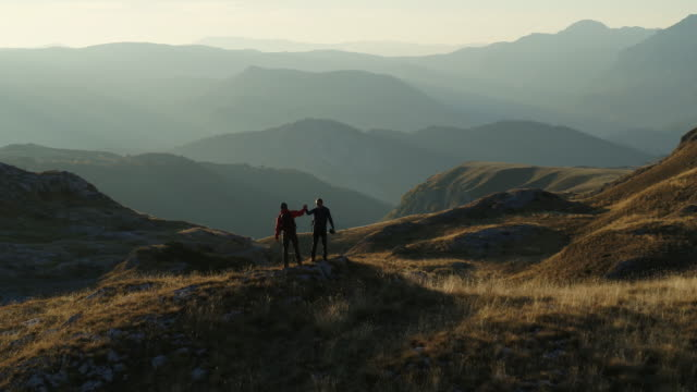 aerial drone shot of two hikers celebrating on top of a mountain vista - stillstehen stock-videos und b-roll-filmmaterial
