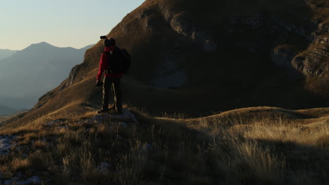 aerial drone shot of two hikers taking a selfie on top of a mountain vista - durmitor national park stock videos & royalty-free footage