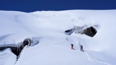 luftdrehkraft-schuss von zwei skifahrern, die ein schneefeld im kaukasus überqueren - herausforderung stock-videos und b-roll-filmmaterial