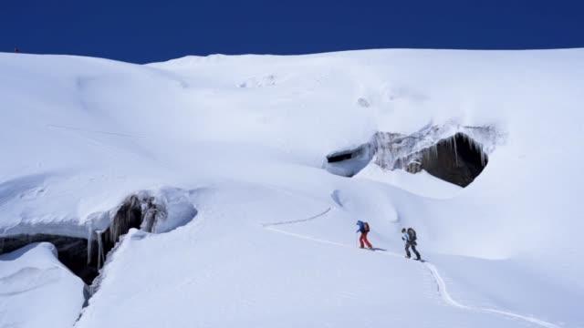 luftdrehkraft-schuss von zwei skifahrern, die ein schneefeld im kaukasus überqueren - hochgefühl stock-videos und b-roll-filmmaterial