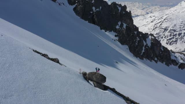 luftdrohne von zwei skifahrern auf einem felsbrocken an der seite eines verschneiten bergrückens - 25 29 jahre stock-videos und b-roll-filmmaterial