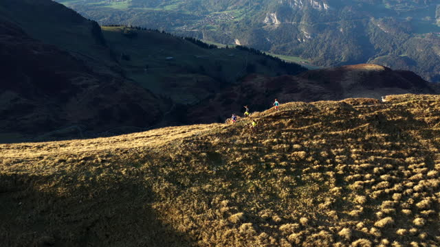 aerial drone shot of two trail runners running along a mountain edge with mountains behind - four people stock videos & royalty-free footage