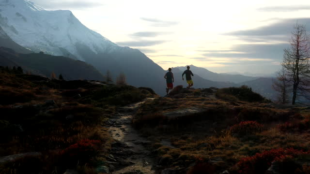 aerial drone shot of two trail runners running along a path in the mountains - at the edge of stock videos & royalty-free footage