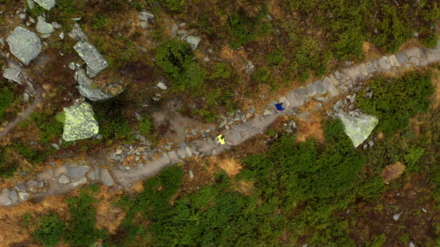 vídeos de stock e filmes b-roll de aerial drone shot of two trail runners running along a stone path in the mountains - beco