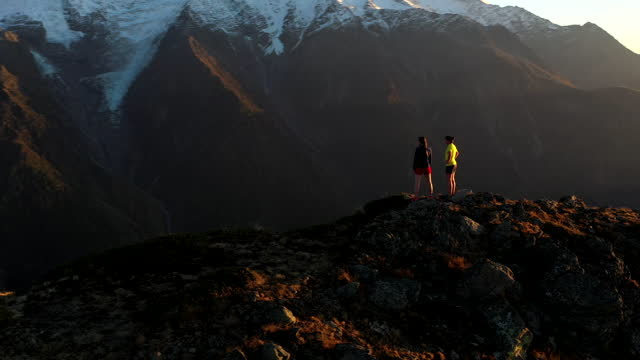 aerial drone shot of two trail runners stopped at the top of a mountain - desire stock videos & royalty-free footage
