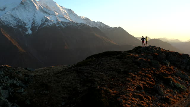 aerial drone shot of two trail runners stopped at the top of a mountain - mountain stock videos & royalty-free footage