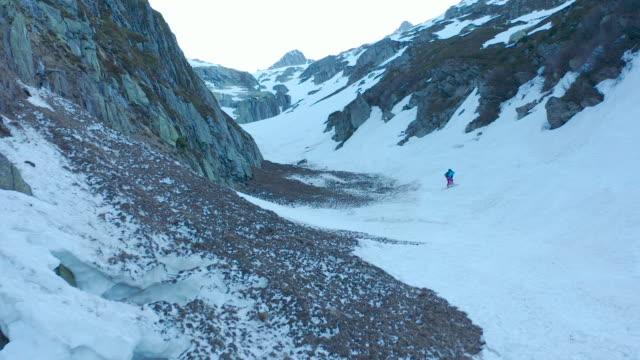vidéos et rushes de drone aérien tiré au-dessus des montagnes enneigées avec des skieurs montant - qui monte