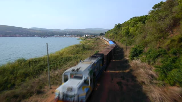 Aerial drone shot passing over a goods train travelling along the shoreline of Lake Tananyika.