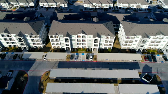 aerial drone side pan across massive apartment condo buildings in new development - flat stock videos & royalty-free footage