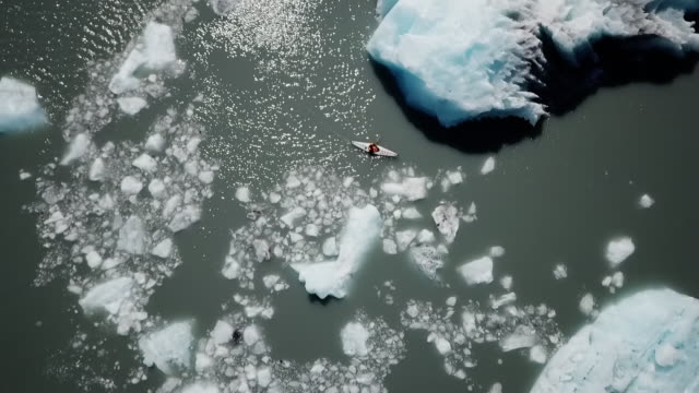 Aerial Drone: Tilt Pan Man Kayaking in Icy Water Near Massive Glacier and Mountains