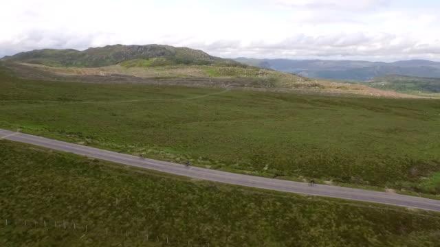 vídeos y material grabado en eventos de stock de aerial / drone tracking shot of a group of cyclists going down a road in the scottish highlands - vehículo de propulsión humana
