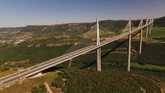 vidéos et rushes de aerial drone traffic passes over millau viaduct - major road