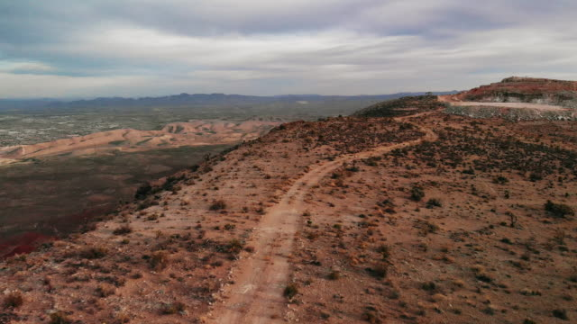 aerial drone trucking forward shot of a dirt road along a desert ridge in red rock canyon national conservation shot of red rock canyon national conservation area next to las vegas, nevada at sunrise/sunset under a cloudy sky - red rocks stock videos & royalty-free footage