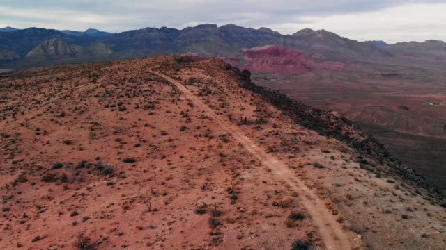vídeos de stock e filmes b-roll de aerial drone trucking forward shot of a dirt road along a desert ridge in red rock canyon national conservation shot of red rock canyon national conservation area next to las vegas, nevada at sunrise/sunset under a cloudy sky - nevada