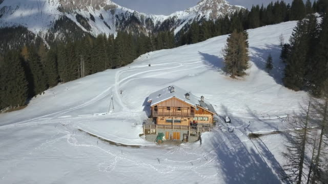 aerial drone uav landscape nature views of a cabin house in snow mountains in the winter. - capanna di legno video stock e b–roll