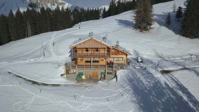 Aerial drone uav landscape nature views of a cabin house in snow mountains in the winter.