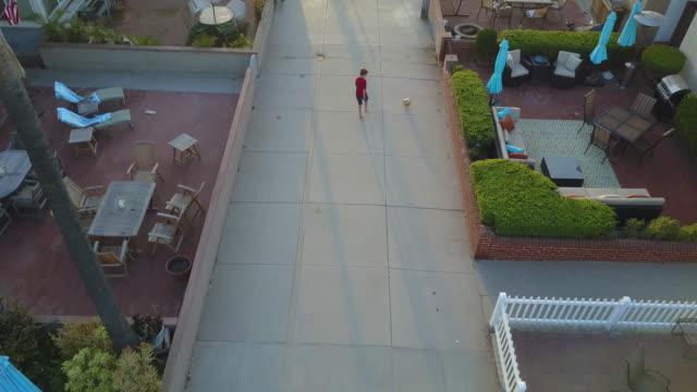 vídeos y material grabado en eventos de stock de aerial drone uav view of a boy playing soccer football on a walk street in a neighborhood. - barra futbol