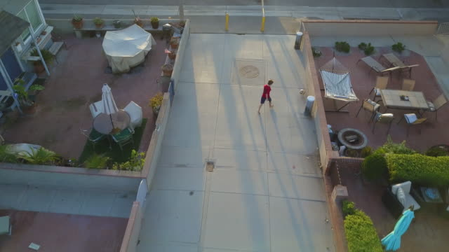 vidéos et rushes de aerial drone uav view of a boy playing soccer football on a walk street in a neighborhood. - ball