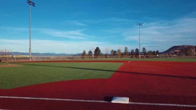 castle rock, colorado/usa - march 28 2019: aerial drone video in the early morning of a freshly prepared local park baseball field ready for baseball opening day play. - baseballfeld stock-videos und b-roll-filmmaterial