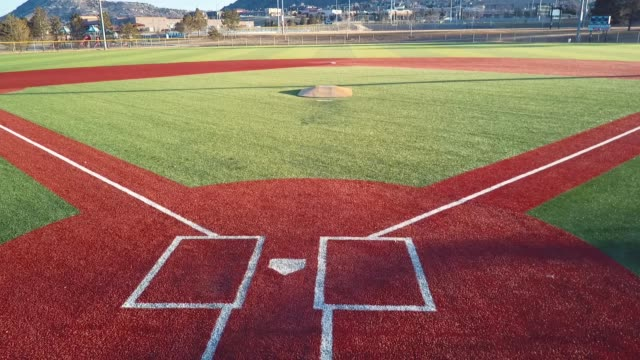 castle rock, colorado/usa - march 28 2019: aerial drone video in the early morning of a freshly prepared local park baseball field ready for baseball opening day play. - 野球ボール点の映像素材/bロール