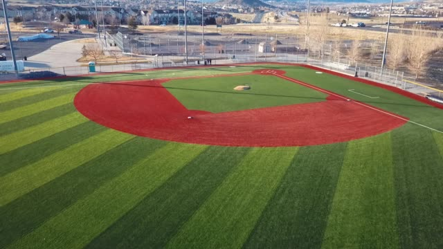 castle rock, colorado/usa - march 28 2019: aerial drone video in the early morning of a freshly prepared local park baseball field ready for baseball opening day play. - 1日目点の映像素材/bロール
