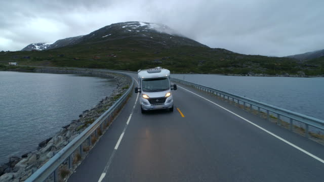 aerial: drone video of camper van drives on highway with beautiful lake - breiddalsvatnet, norway - people carrier stock videos & royalty-free footage