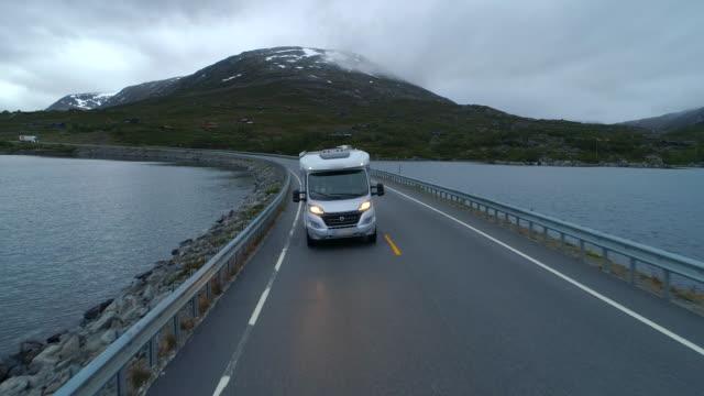 aerial: drone video of camper van drives on highway with beautiful lake - breiddalsvatnet, norway - van stock videos & royalty-free footage