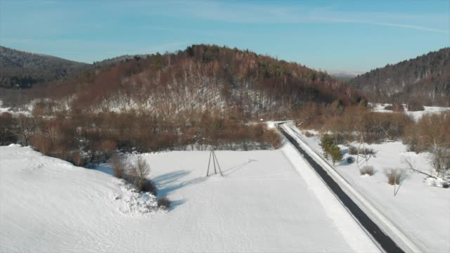 aerial drone view a snow covered street and winter road trail. - winter stock videos & royalty-free footage