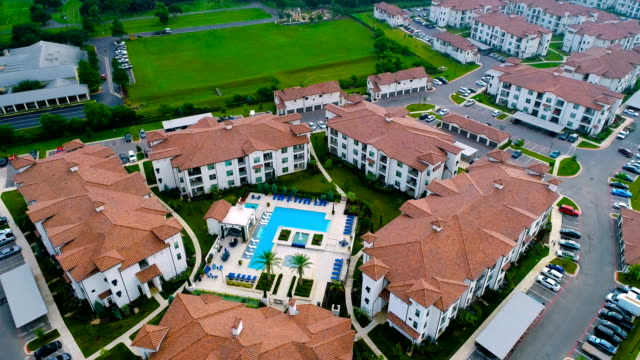 aerial drone view above apartment complex with orange rooftop and modern swimming pool - flat stock videos & royalty-free footage