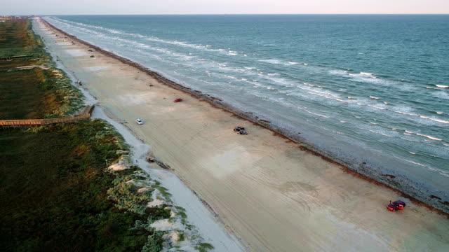 aerial drone view above padre island coasting along the sand and waves a paradise beach awaits port aransas , corpus christi , texas , gulf of mexico coast - corpus christi texas stock videos & royalty-free footage