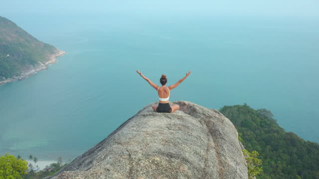 aerial drone view and rear view,happy of young women age 29 yearold of latin american and hispanic ethnicity doing practice yoga on the top of mountain ocean summit.happiness in nature concept. - wonderlust stock videos & royalty-free footage