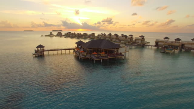 Aerial drone view at sunset of a scenic tropical island and resort hotel with overwater bungalows in the Maldives.