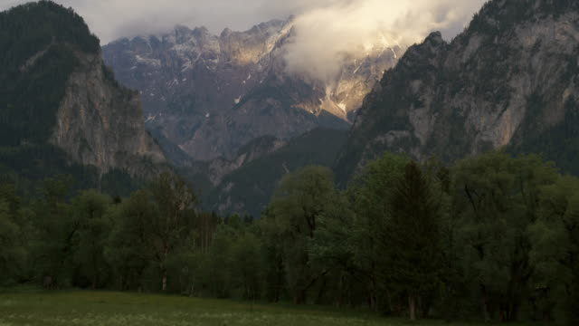 stockvideo's en b-roll-footage met aerial drone view at sunset of peaks surrounded by clouds with forest below - sneeuwkap