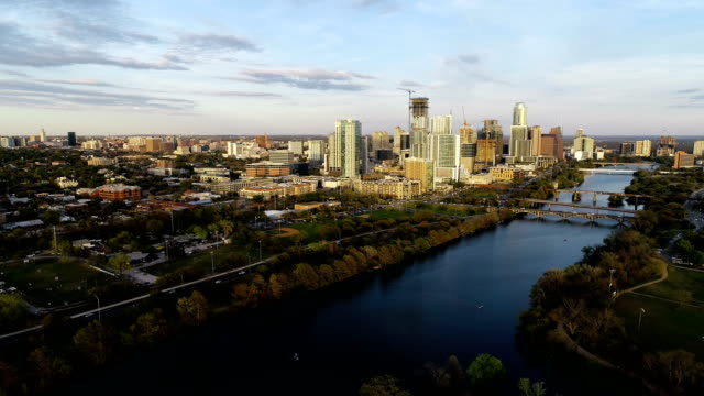 vídeos de stock e filmes b-roll de aerial drone view backing away from downtown golden view of skyline cityscape with town lake - town