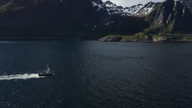 aerial drone view: fishing boat at lofoten islands in norway - fishing boat stock videos & royalty-free footage