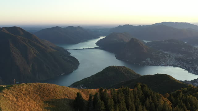 vídeos de stock e filmes b-roll de aerial drone view flying over mountain ridge at sunset revealing lake lugano - suíça