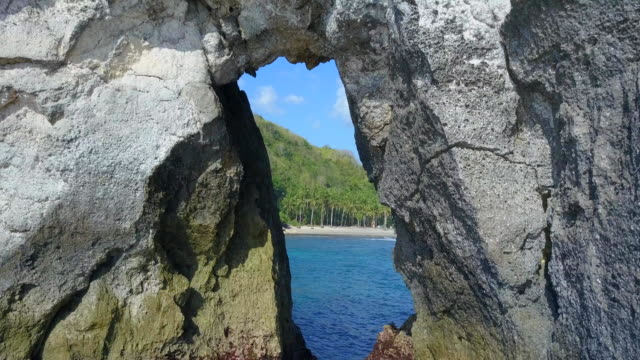 aerial drone view flying through a natural rock arch the beach. - natural arch stock videos & royalty-free footage