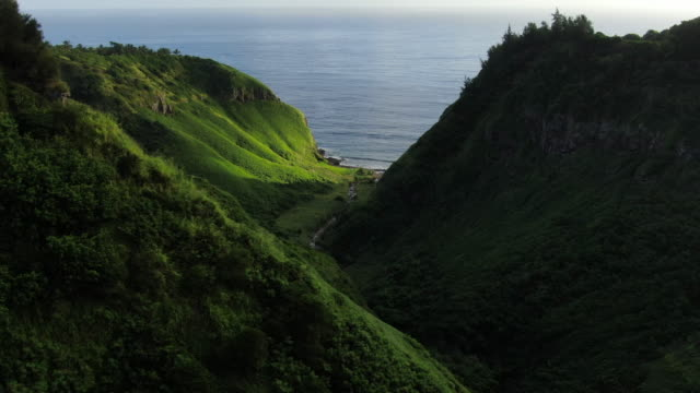 vidéos et rushes de aerial drone view flying through valley towards ocean - site naturel
