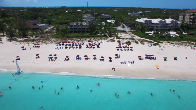 Aerial drone view from the sea of the beach filled with tourists / Provodenciales, Turks and Caicos Islands