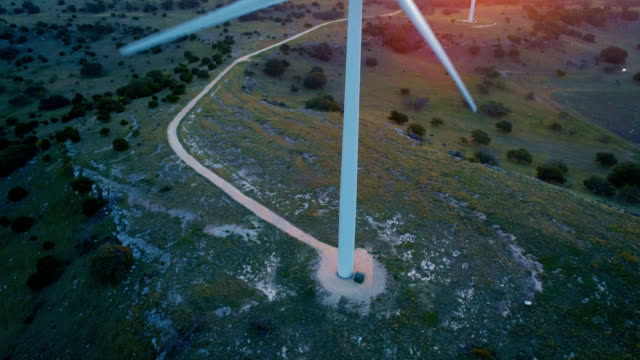 aerial drone view looking down at ground camera pan up to silhouette golden hour sunlight beams across wind turbine - wind turbine stock videos and b-roll footage