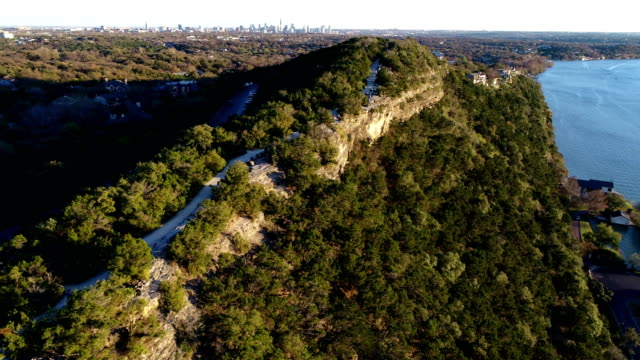 Aerial Drone view looking up the Ridge of Mount Bonnell with Austin , TX in the background near sunset