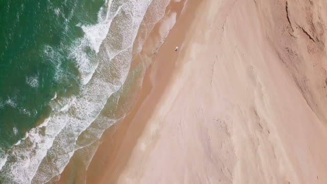 vídeos de stock, filmes e b-roll de aerial drone view of a 4x4 jeep car vehicle driving on the beach surf trip. - ponto de vista de carro