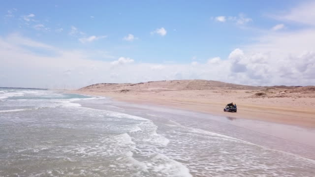 Aerial drone view of a 4x4 jeep car vehicle driving on the beach surf trip.
